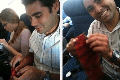 man knitting on plane and smiling