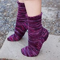Purple toe-up socks with heel flap, shown from the side, on tip-toe