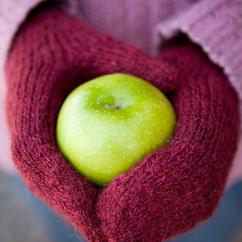 Red worsted-weight magic loop mittens with hands holding a green apple