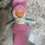 Doll wearing pink socks as sleeping bag and slouchy hat Leila S.