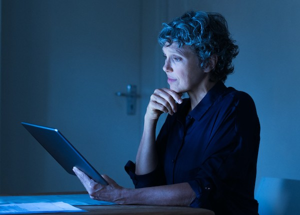 Senior woman working on screen late at night