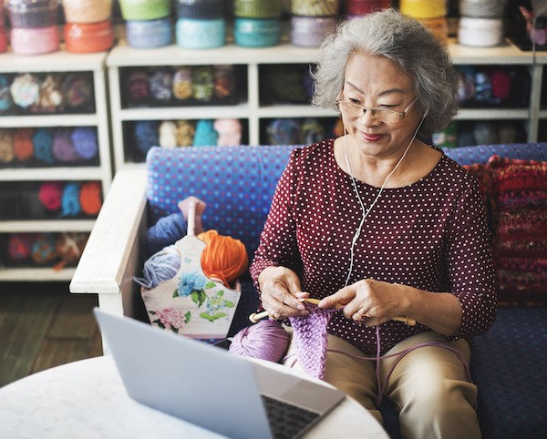 Happy woman sitting at computer in yarn shop knitting